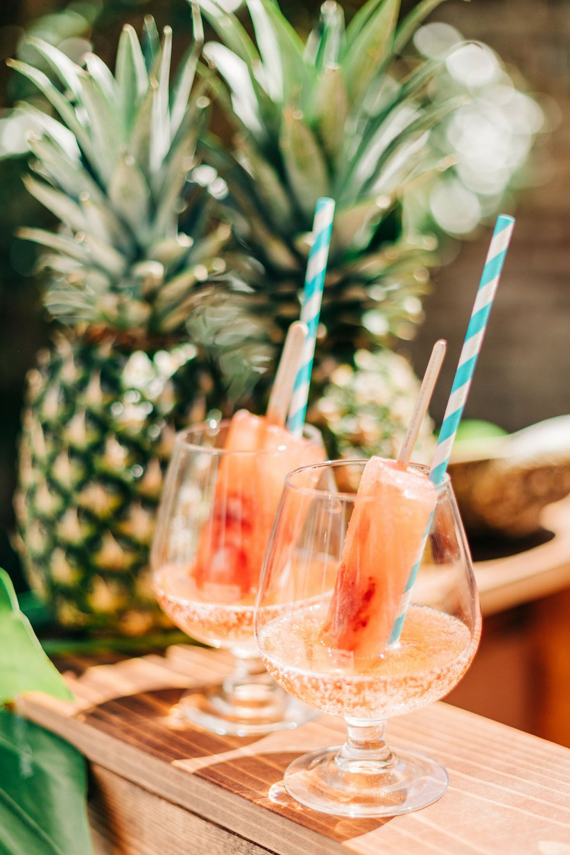 glasses with fruit popsicles in sparkling wine and turquoise paper straws