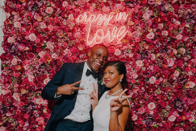 groom and bride standing in front of flower wall with crazy in love neon sign