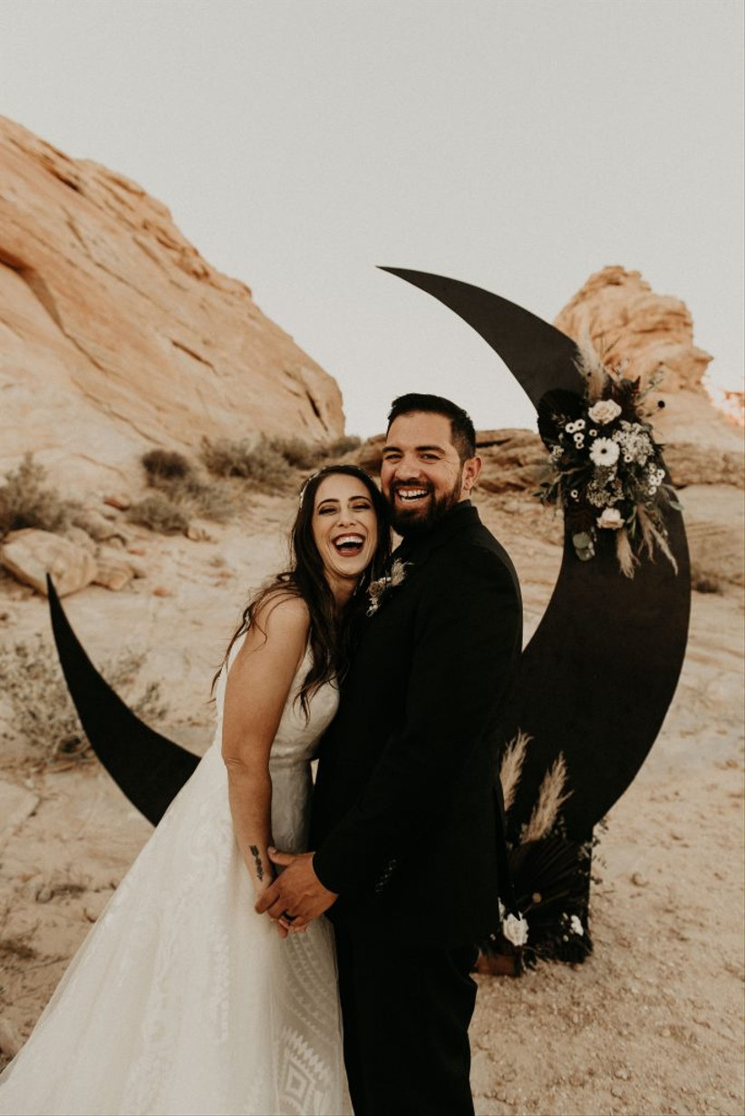 bride and groom smiling at the camera desert wedding venue with boho crescent moon photo backdrop