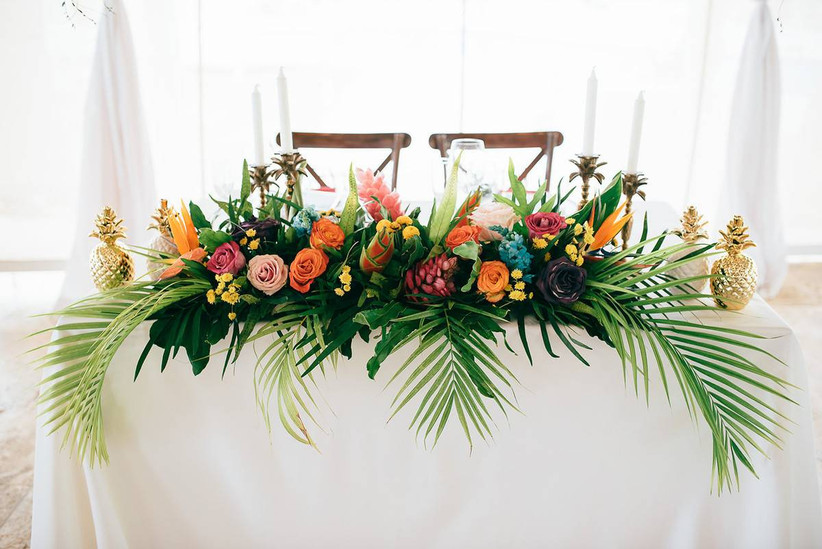 sweetheart table centerpiece with large palm leaves, orange and pink roses, birds of paradise, and golden metal pineapples