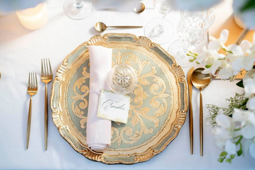 overhead shot of reception place setting with gold and sage green patterned plate and gold utensils