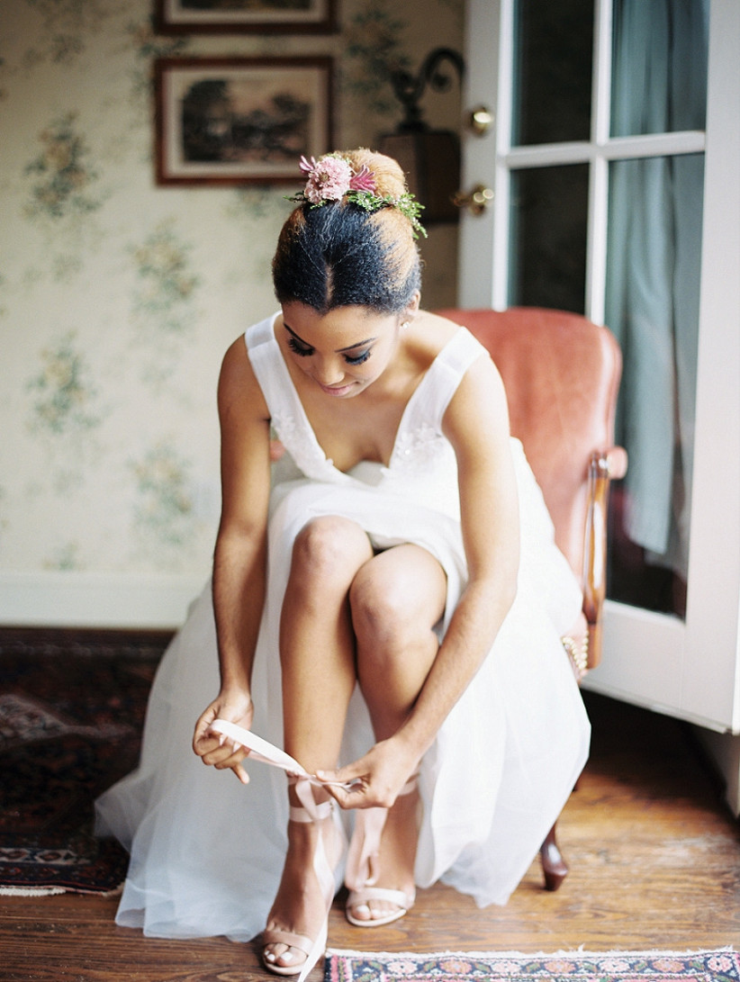 Black bride is seated while fastening ankle straps on her high heels with fresh flowers adorning her sleek bun hairstyle