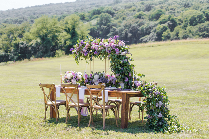 small outdoor wedding reception table decorated with purple and greenery garland