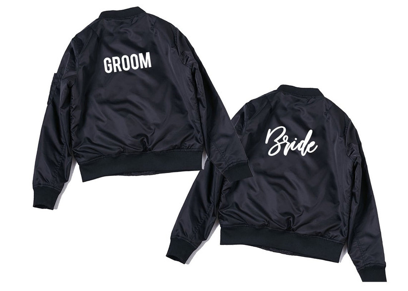 black windbreaker bomber jacket with white cursive text that reads