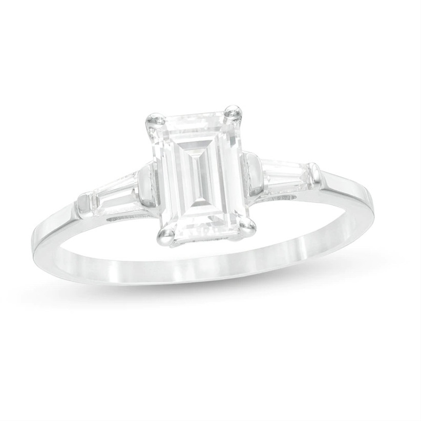 three stone engagement ring with emerald cut stone