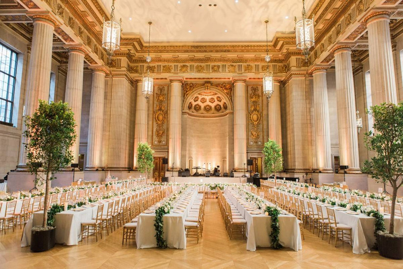 wide shot of ballroom wedding reception venue with pillars along both sides of the room and opulent gold carved ceilings