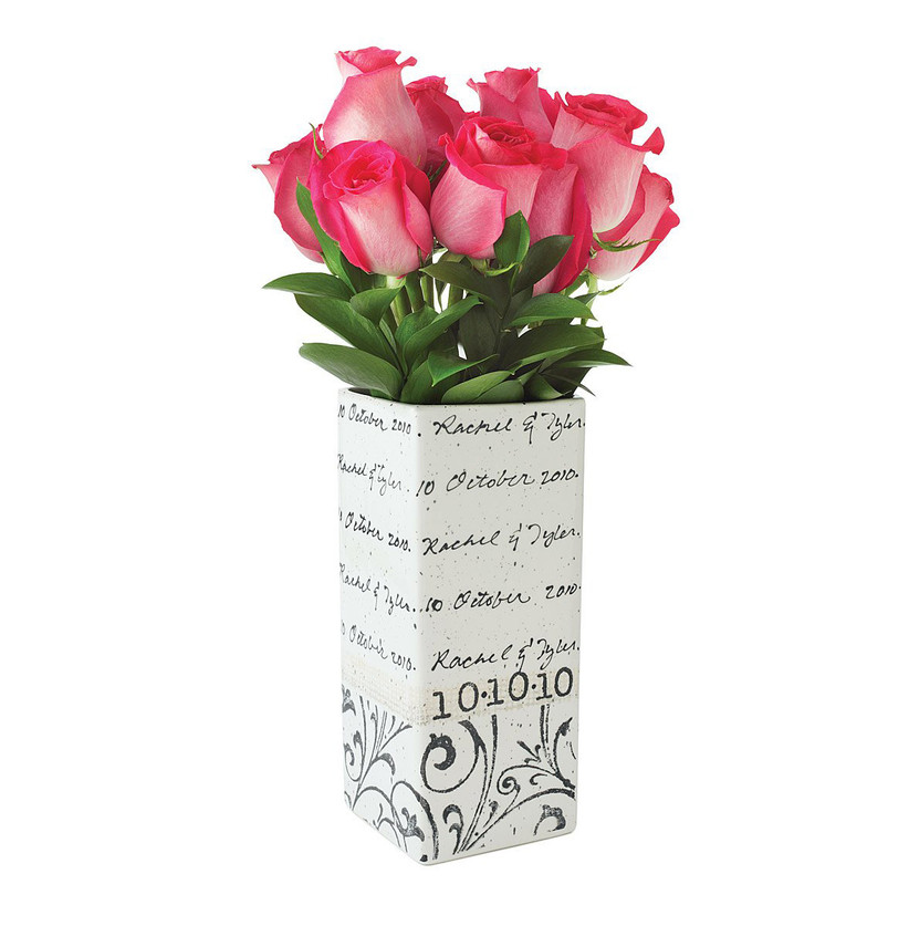 White rectangular vase with black cursive design filled with pink flowers