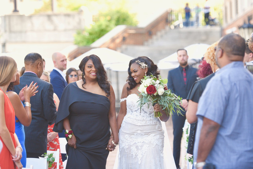 bride smiles as she walks down the ceremony aisle with her mom
