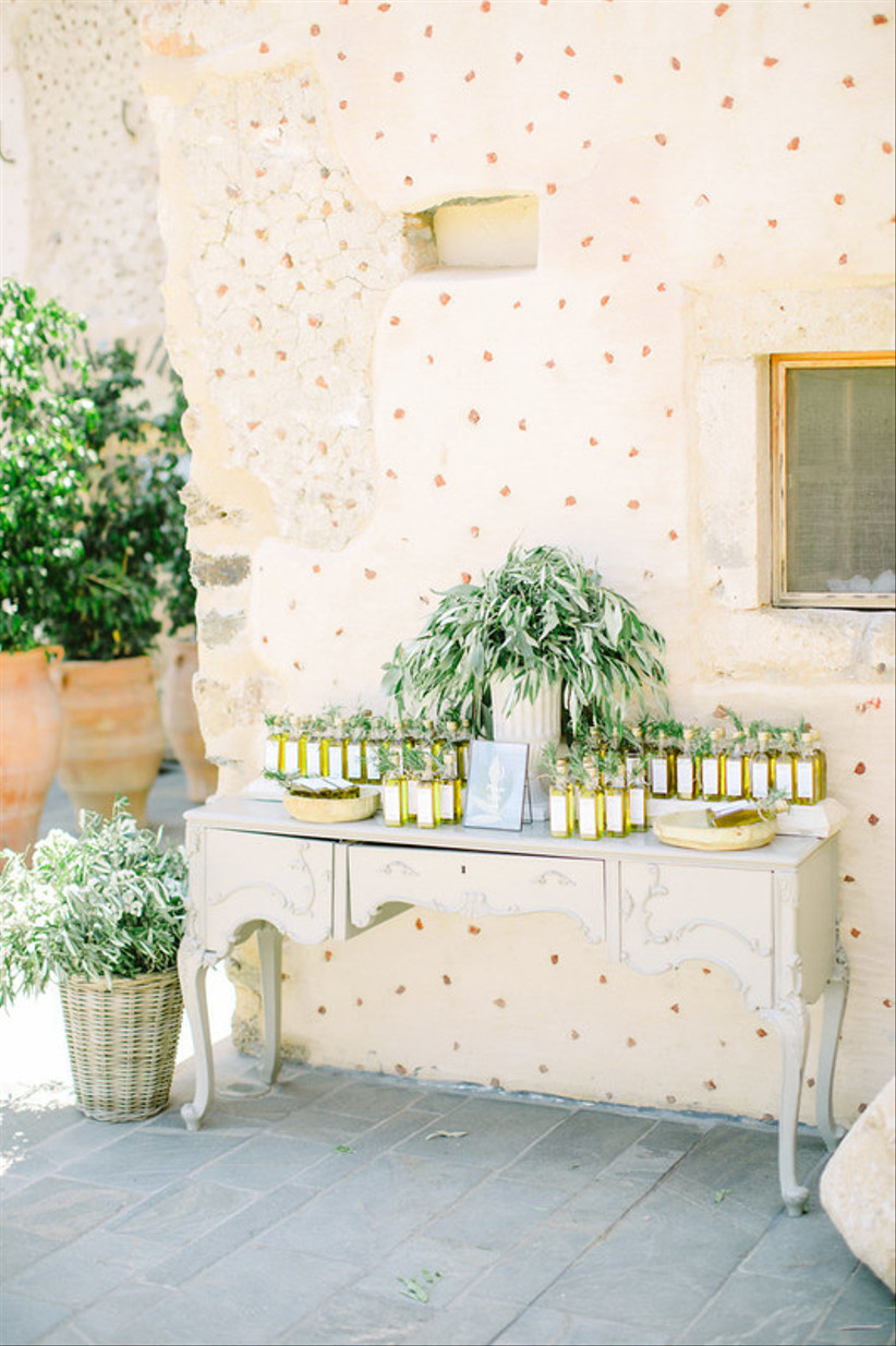 vintage buffet table decorated with olive oil escort card/favors and greenery
