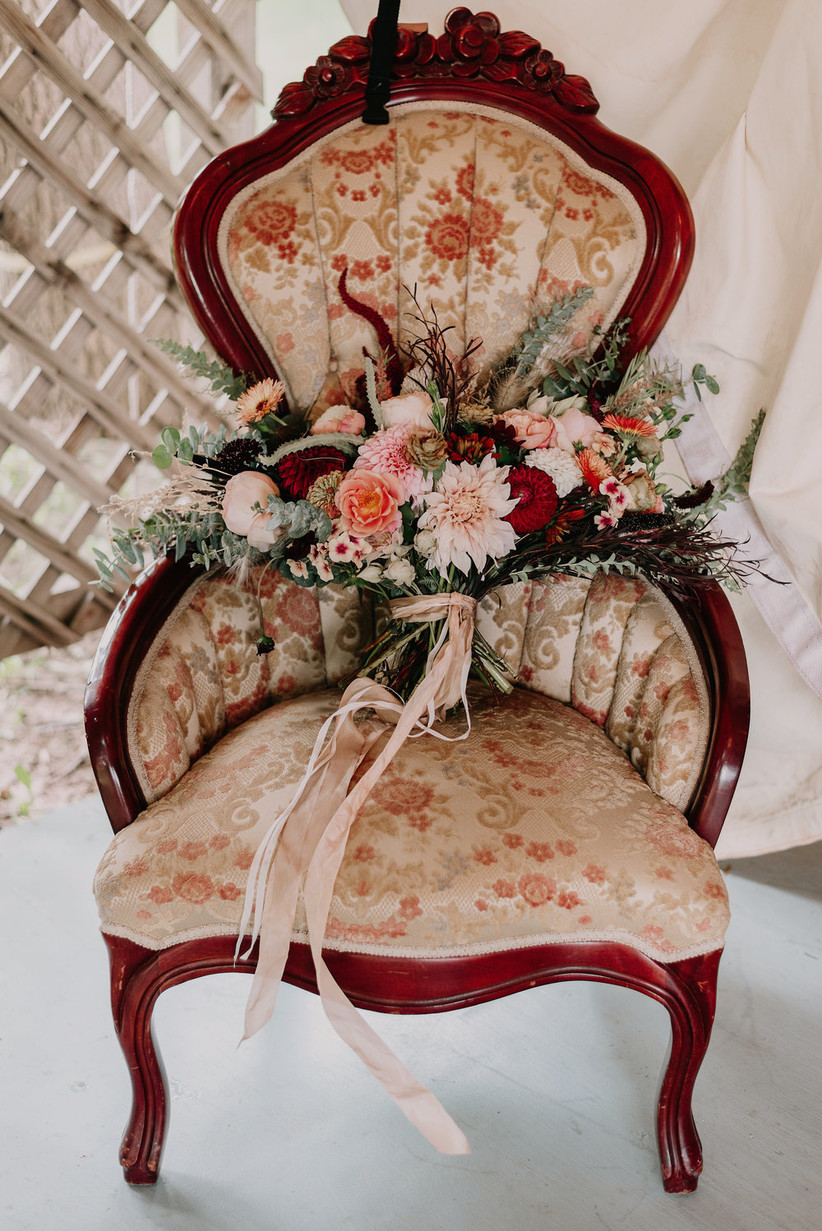 burgundy, pink, and green fall wedding bouquet on a vintage upholstered chair