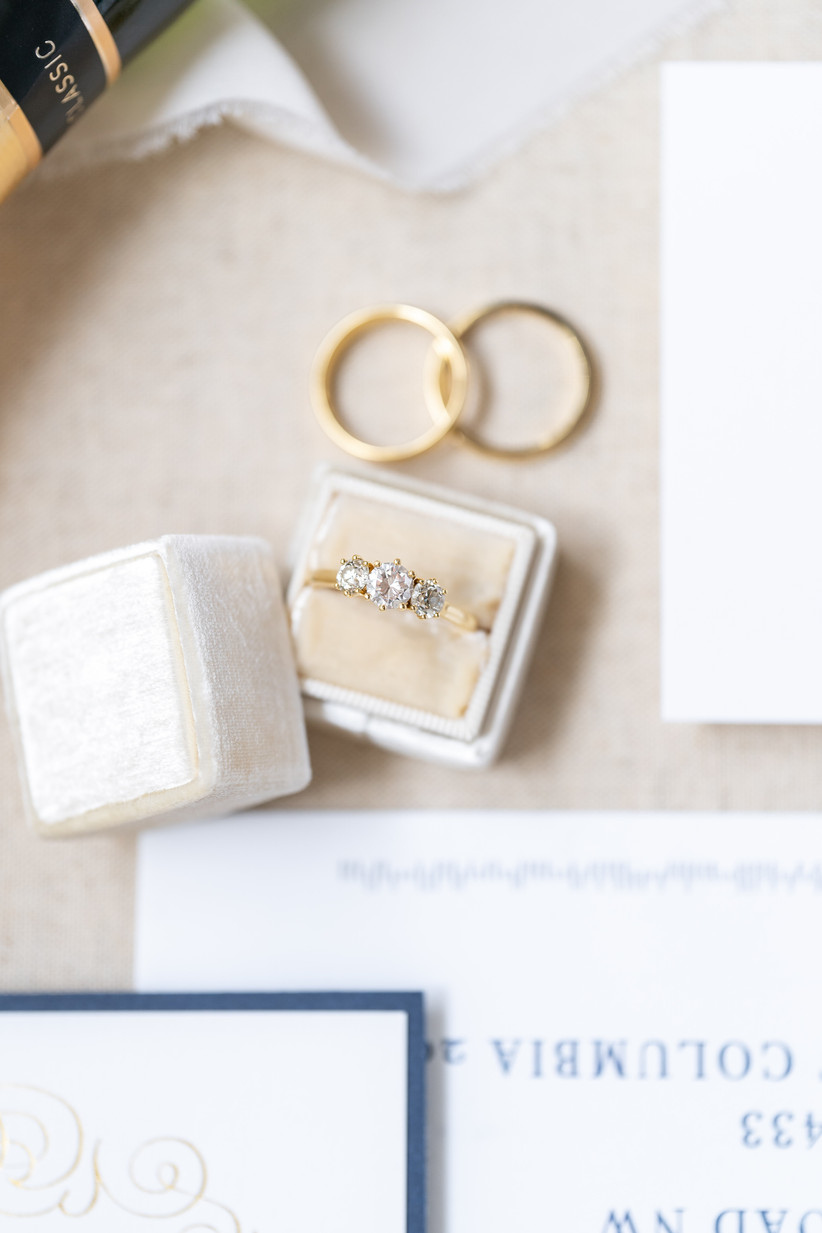 three-stone engagement ring trend with round diamonds in yellow gold setting