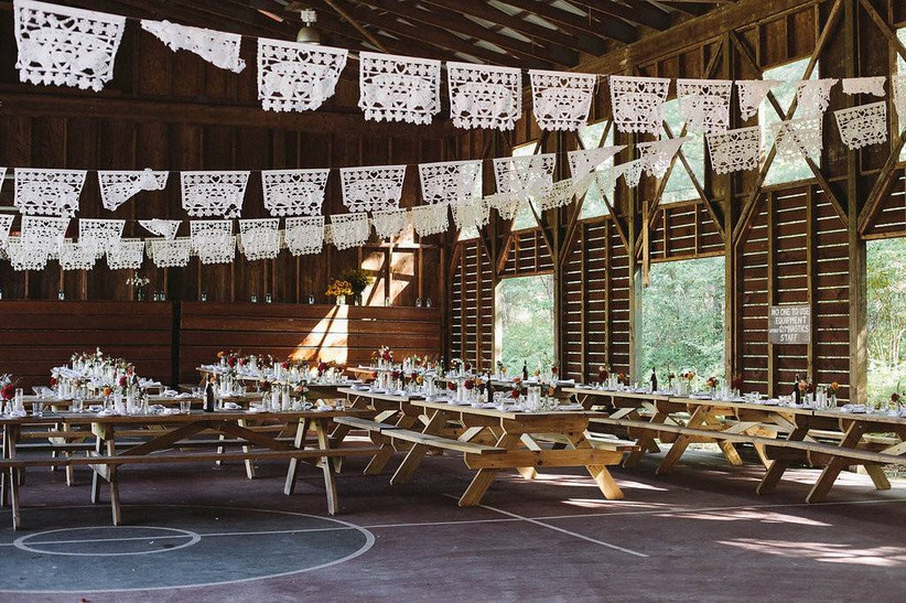 wedding reception set up with wooden picnic tables and paper garlands
