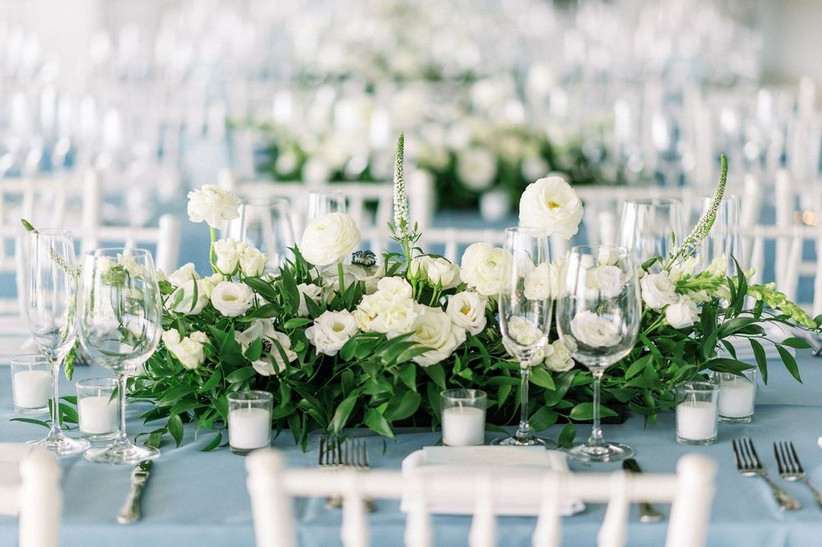 monochromatic white beach wedding centerpiece with ranunculus, lisianthus, and greenery on pale blue tablecloth