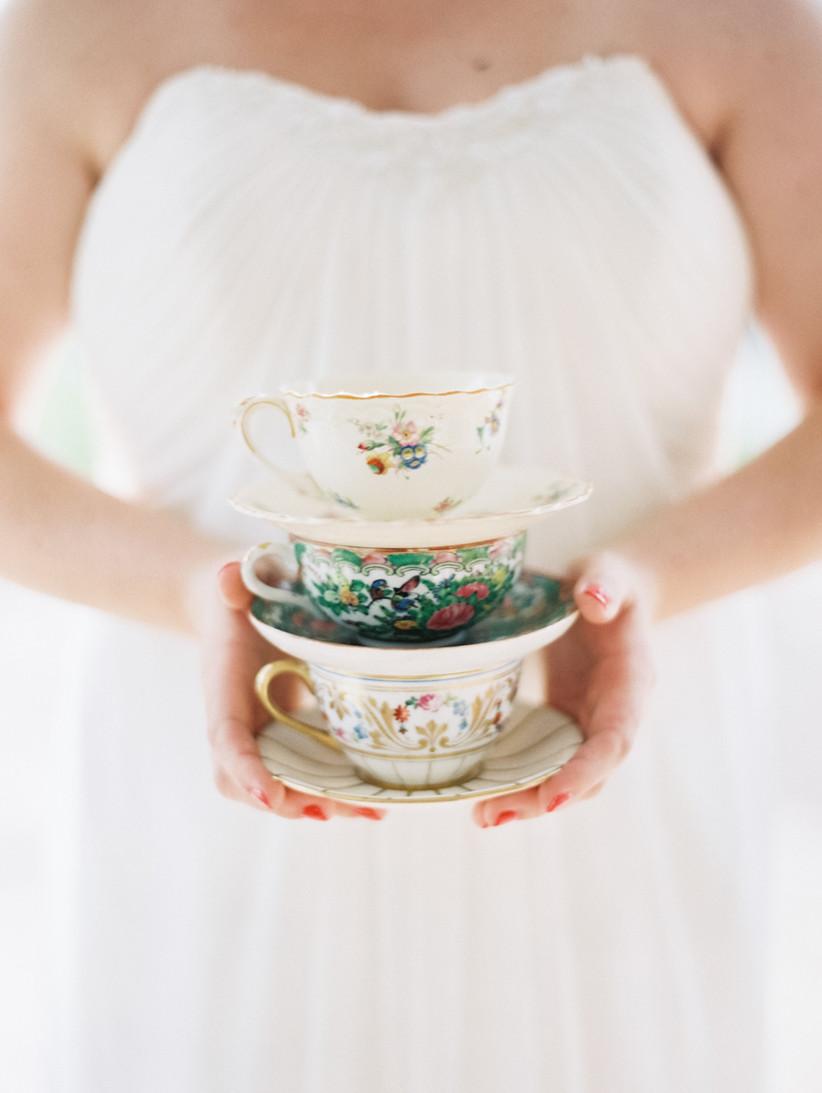 close-up of vintage teacup stack in bride's hands
