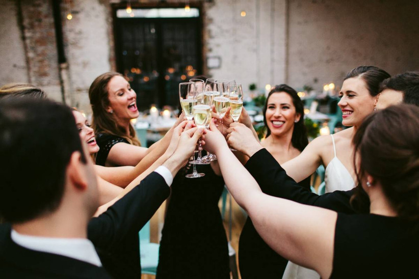 group of wedding partygoers toasting champagne