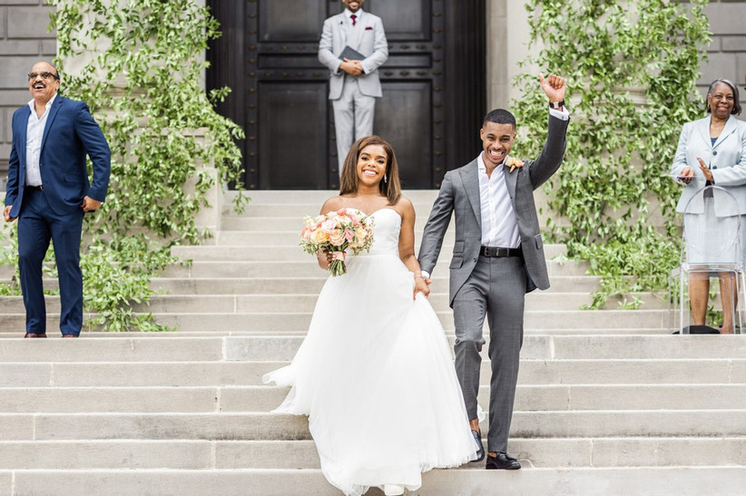 smiling Black couple celebrates as their wedding guests cheer while standing on the steps of a church