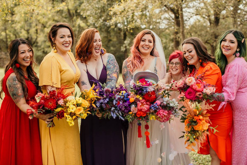 bride stands with her bridesmaids wearing dresses in rainbow colors