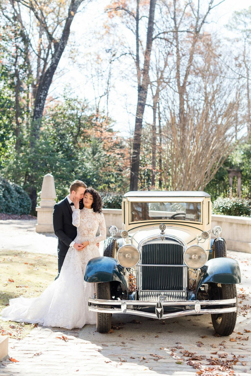 bride and groom stand outside next to antique car