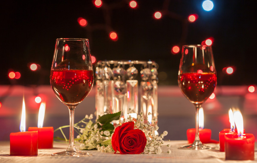 Romantic table setting with wine glasses, red candles, and a rose
