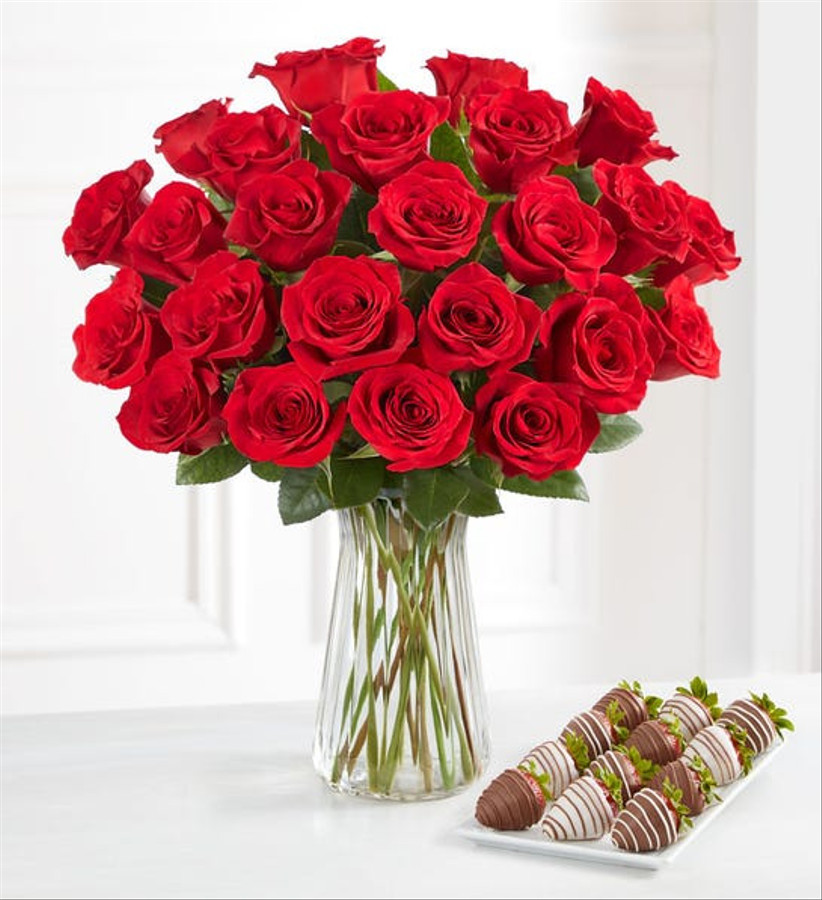 bouquet of red roses next to plate of chocolate covered strawberries