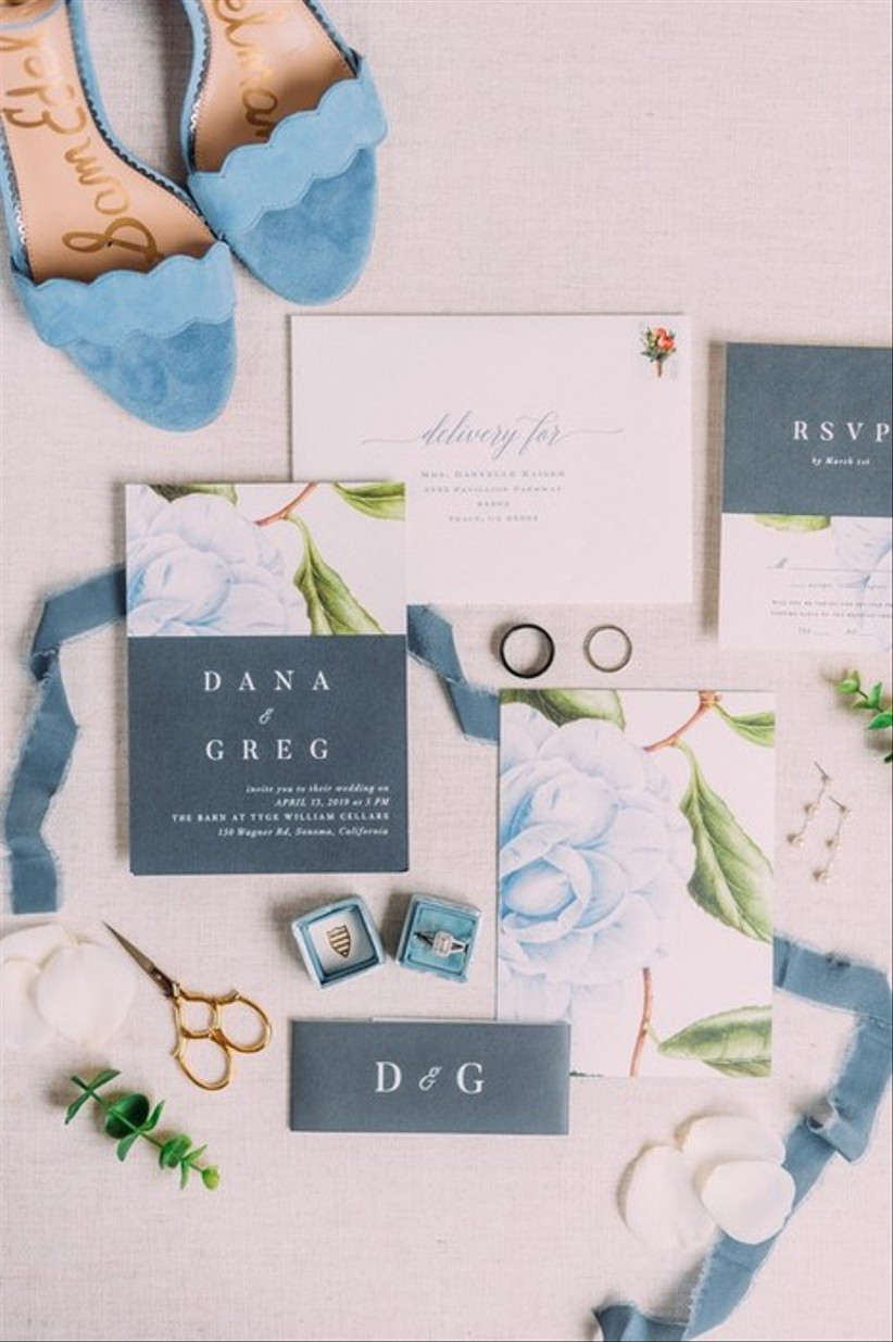blue wedding flat lay with floral invitations and blue velvet ring box