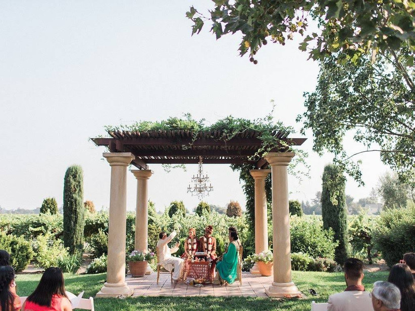 South Asian wedding taking place under stone pergola with vineyard views in the background