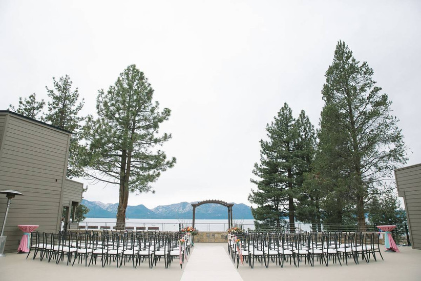 spacious outdoor wedding ceremony overlooking the lake and trees in the distance
