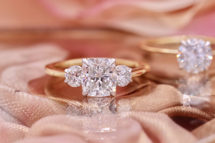 three-stone engagement ring trend with cushion cut stone and yellow gold band