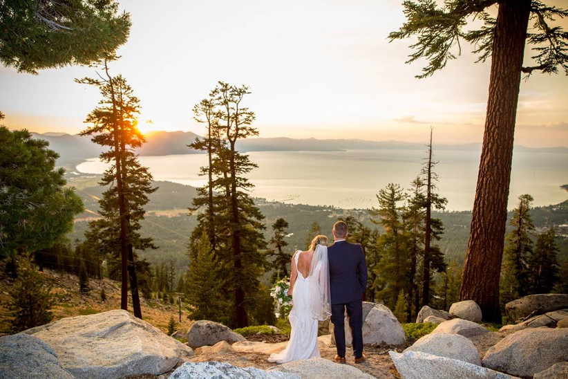 bride and groom standing on rocky mountaintop overlooking valley