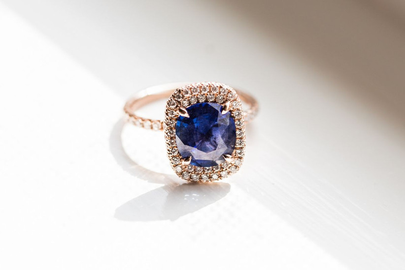 cushion-cut blue engagement ring with yellow gold double halo setting and thin pave band