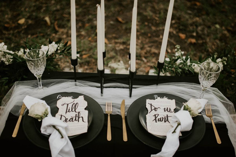 gothic wedding reception tablescape with black plates gold flatware and signs made from book pages that say
