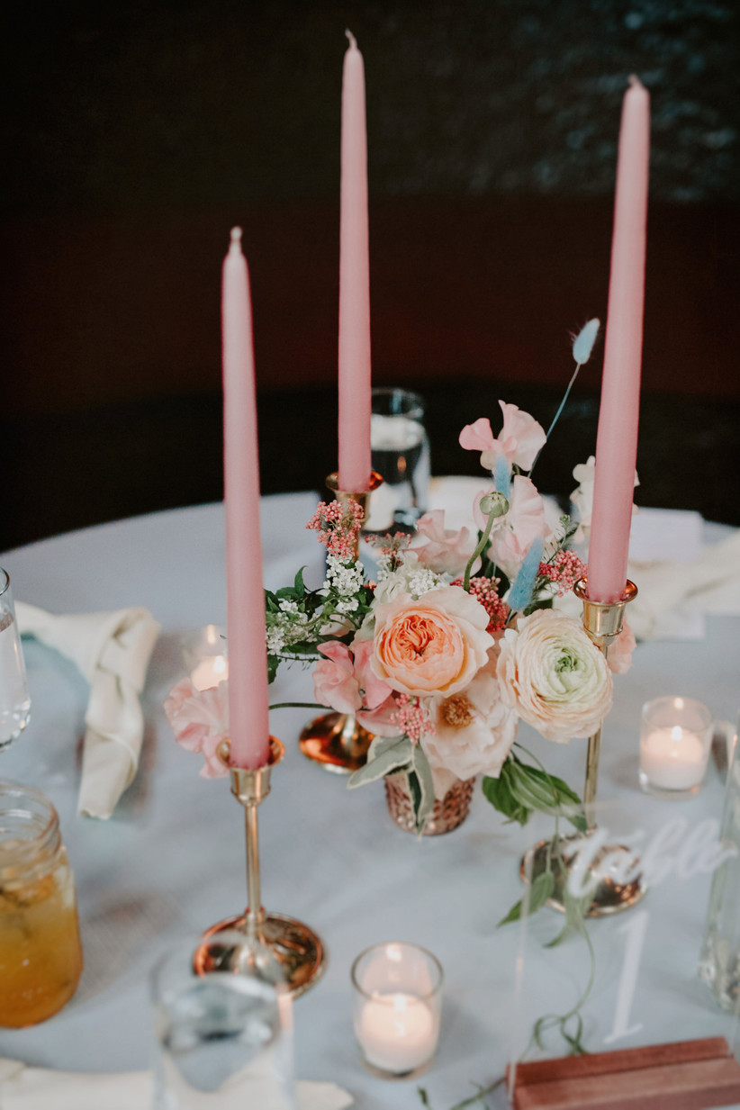 wedding centerpiece with tall pink taper candles in gold candlesticks