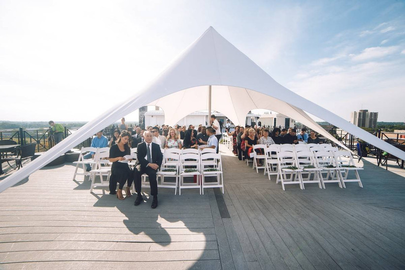 outdoor wedding ceremony with white modern tent