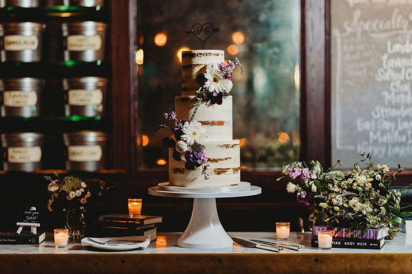 three-tier buttercream wedding cake on table with votive candles,vintage book stacks, and small flower arrangements