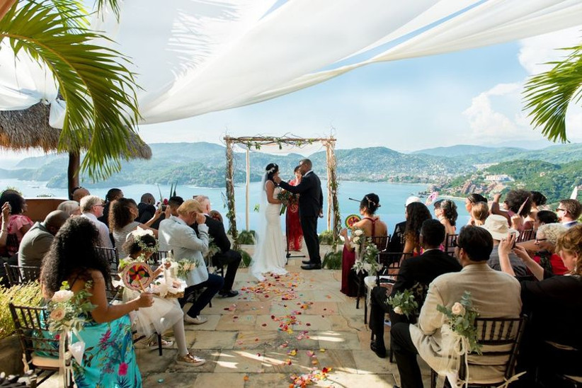 Tropical outdoor wedding with couple standing in front of an arch and guests in seats