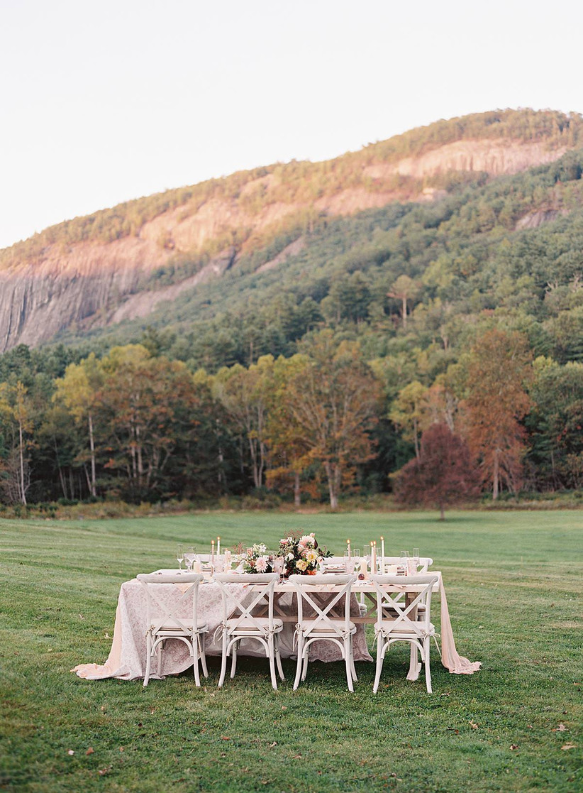 empty wedding reception table is set up outside in a field with a sunny view of mountains in the background