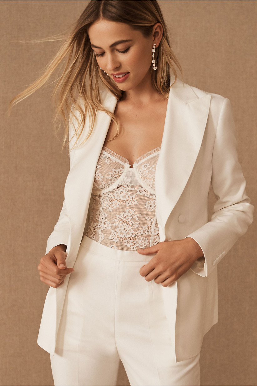 relaxed fit ivory suit jacket paired with lace bustier top and matching dress pants