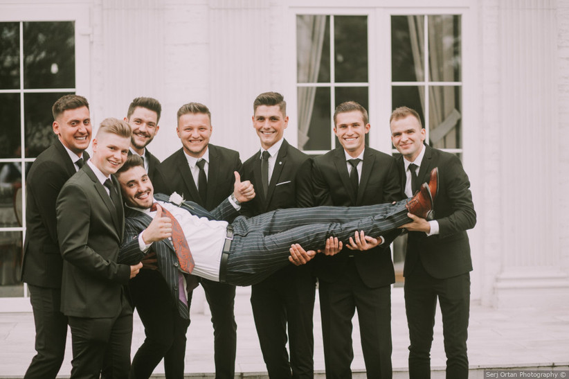 group of groomsmen carry groom for a silly wedding photo