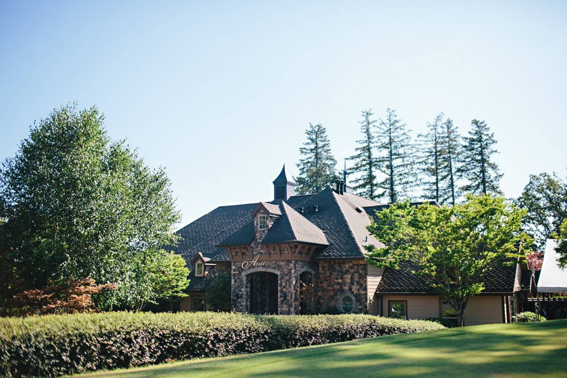 wedding venue in oregon elegant dark stone building surrounded by trees and manicured lawns