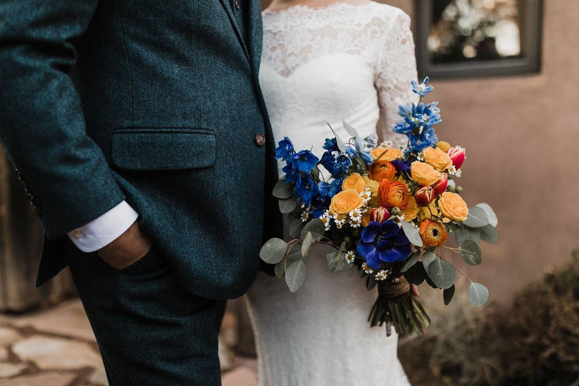 rainbow wedding theme bouquet with blue, orange, yellow, and red flowers