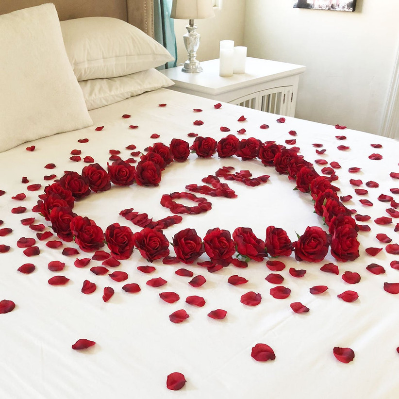 Rose petals on a bed spelling out Love surrounded by a heart