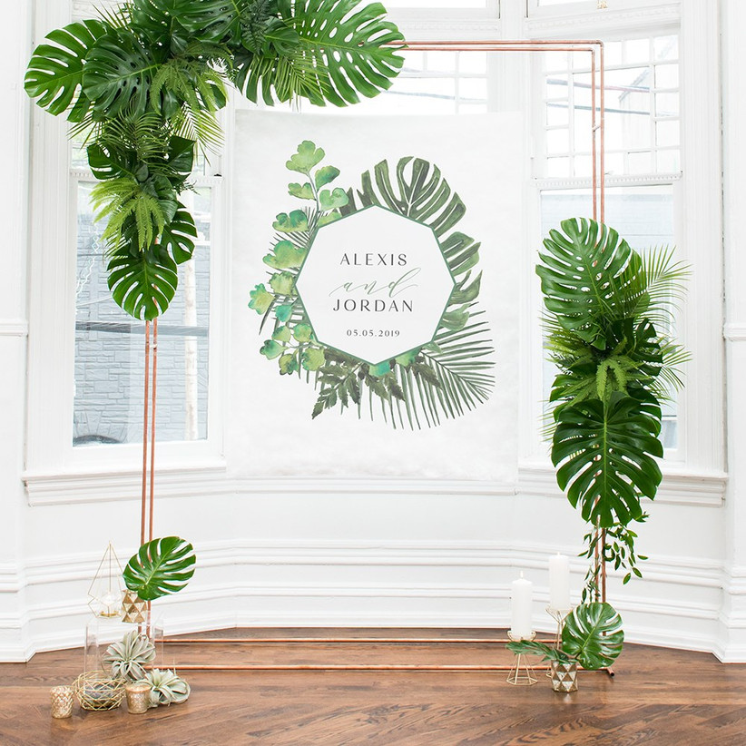 Tropical bridal shower backdrop personalized with couple's names and the date set up in light, airy room