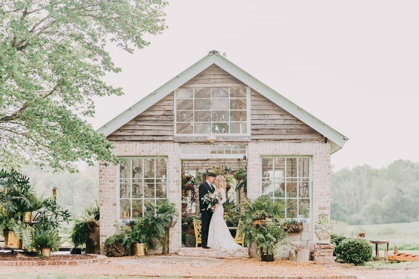 bride and groom pose in front of vintage brick greenhouse with plants overflowing
