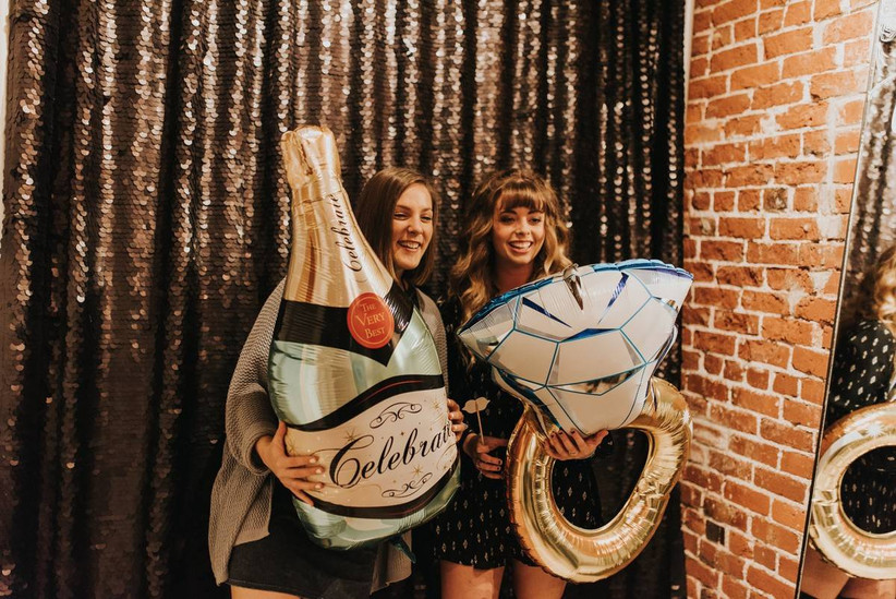 two young women in a photobooth holding balloons