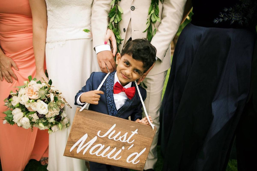 close up of ring bearer posing with wedding party and holding