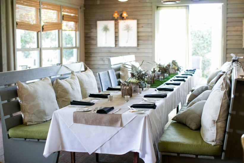 intimate wedding reception table with bench seating, throw pillows, and small floral centerpieces