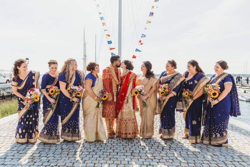 bride and groom kiss wearing traditional indian wedding attire while standing with bridesmaids in front of flagpole with nautical flags