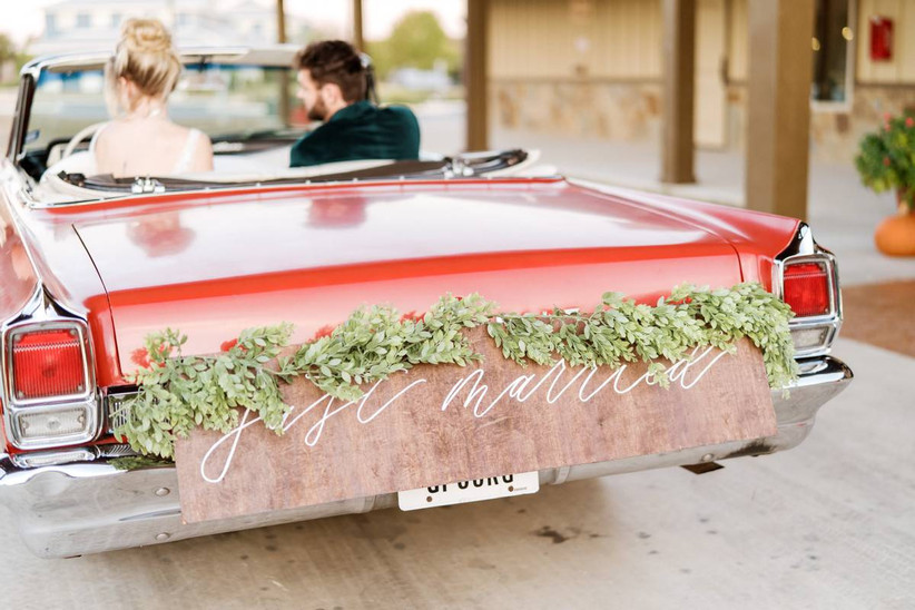 """vintage 1960s convertible with wooden """"just married"""" sign decorated with greenery garland on the bumper"""