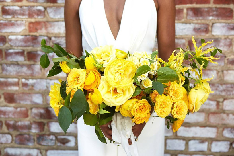 Black bride holding monochromatic yellow beach wedding bouquet with garden roses, ranunculus and greenery