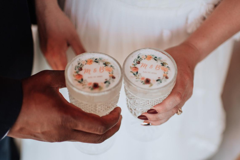 couple holding cocktails that are topped with their monogram and wedding date